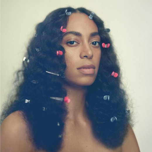 """Image: """"A Seat at the Table"""" album cover, Solange Knowles from the shoulders up with alternating pink and light blue clips in her hair"""